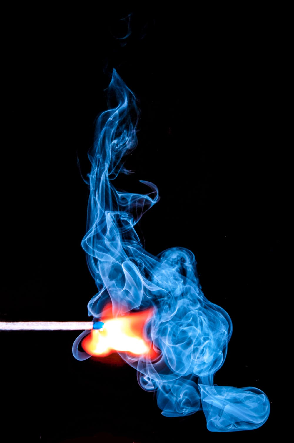 matchstick on fire with red and blue flames.
