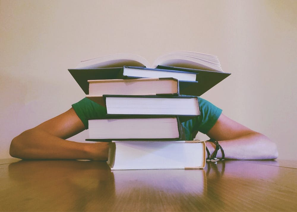 Person behind stack of books