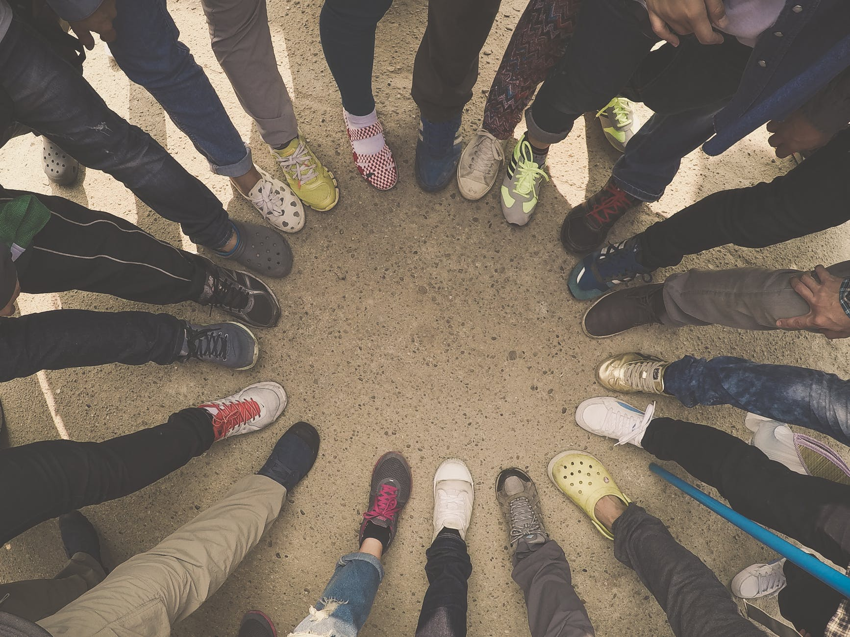 View from above- circle of people with one leg each in a circle. Shoe circle.
